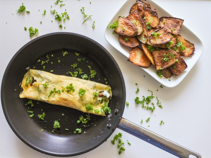 A French omelette garnished with chopped parsley in a pan served alongside roast potatoes