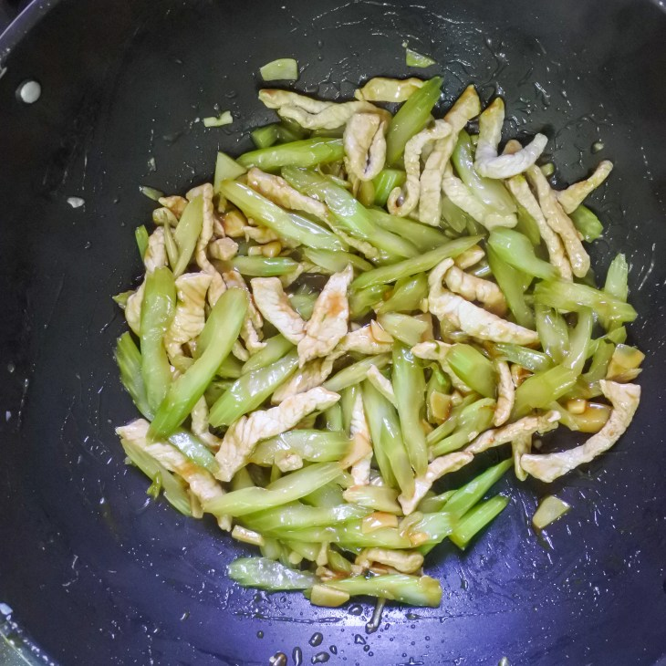 pork and celery frying in wok with sauce