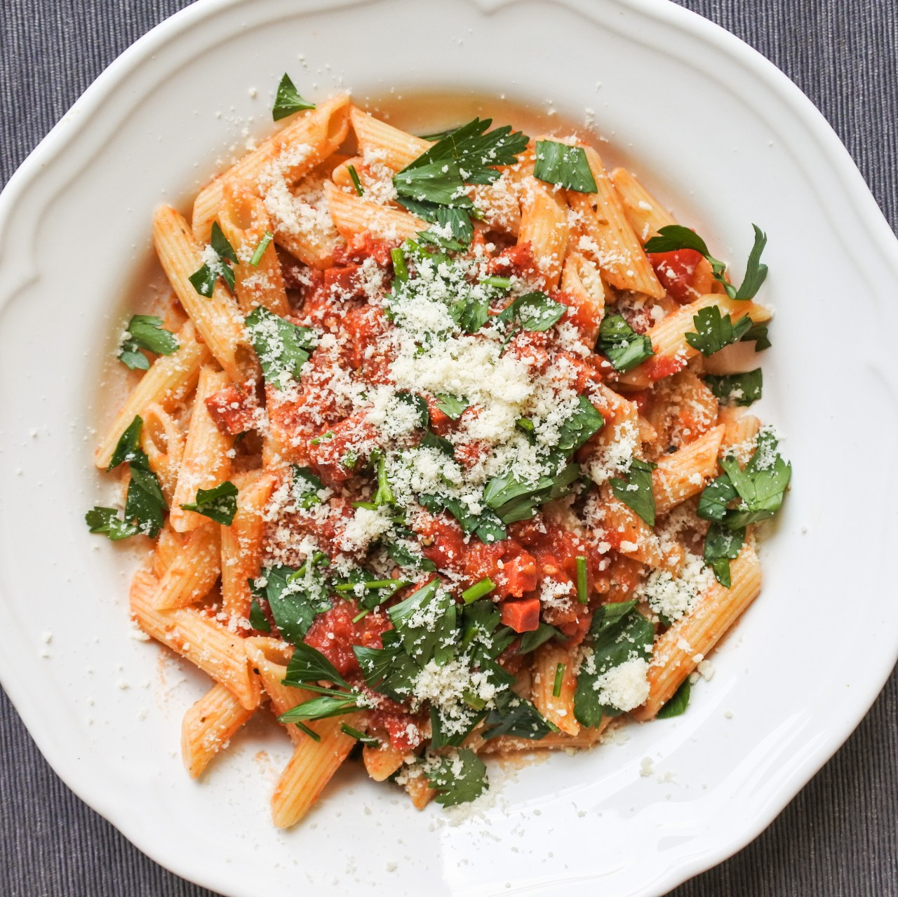 Penne pasta covered in a tomato and chorizo sauce and garnished with chopped Italian parsley and grated cheese