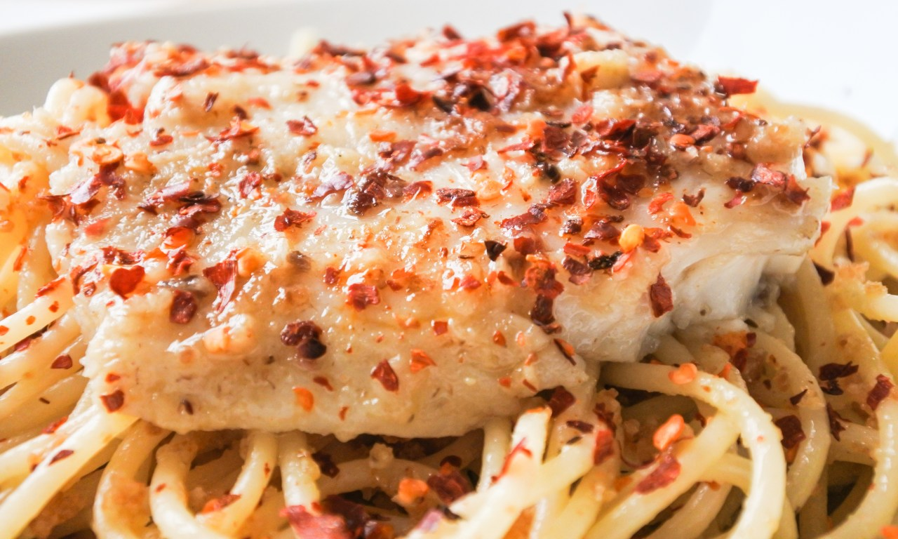 A bowl of spaghetti tossed in breadcrumbs and anchovy sauce then topped with white fish and red pepper flakes