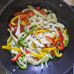 Strips of bell peppers and onions frying in a large skillet