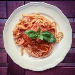 A plate of fettuccine covered in red sauce and garnished with Basil leaves