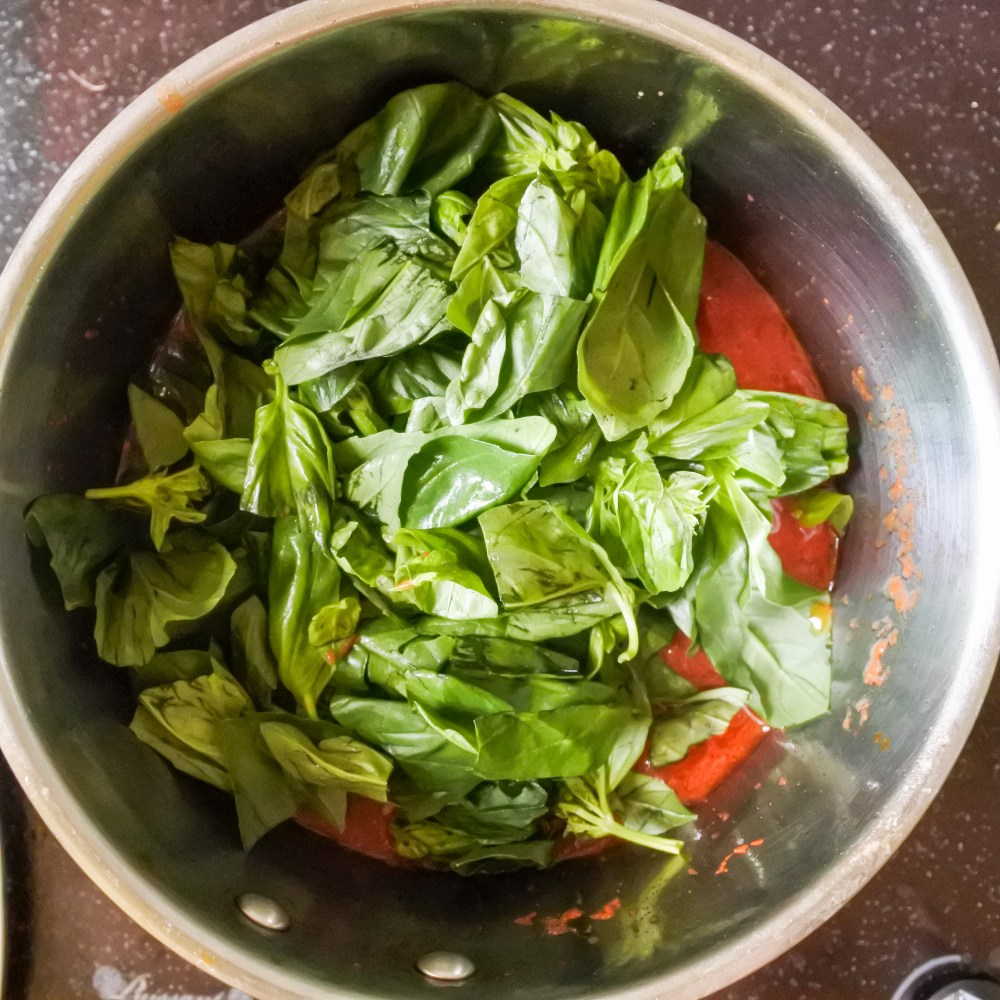 Torn fresh Basil leaves going into a saucepan of red sauce