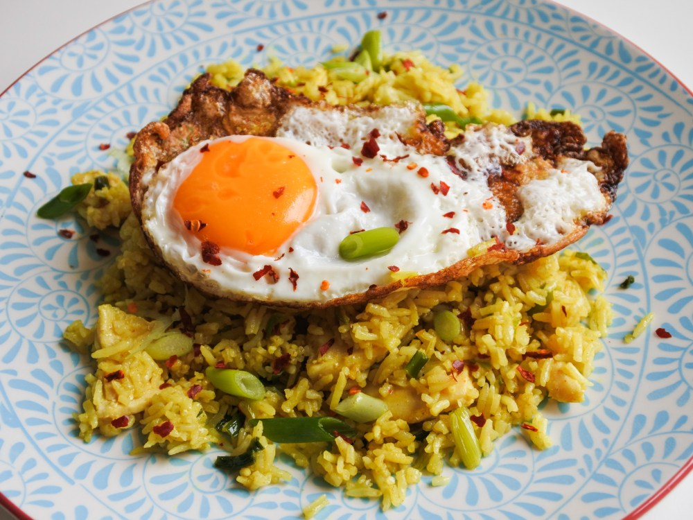 A sunny side up egg atop a pile of curried rice and fish garnished with chopped scallions on a blue plate