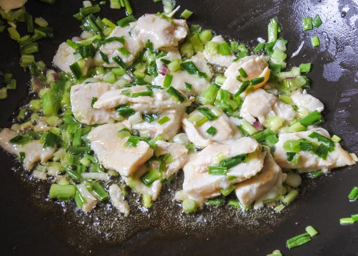 Smoked fish and chopped scallions cooking in butter in a large pan