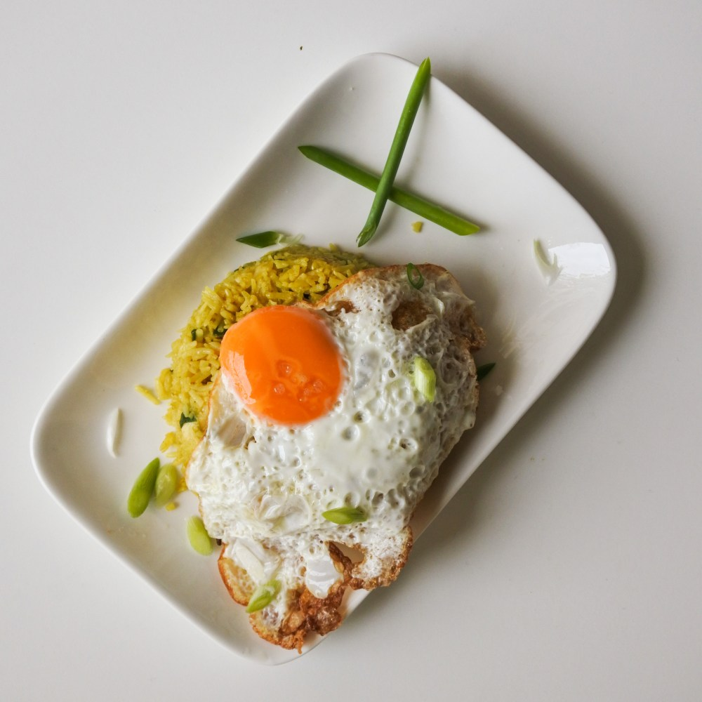 A sunny side up egg atop a mound of kedgeree on a rectangular white plate