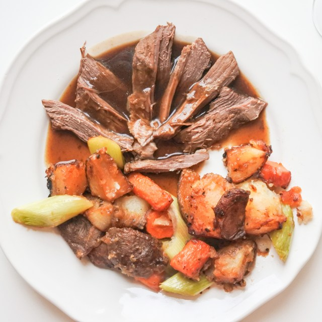 Strips of brisket covered in a dark gravy on a plate with roasted root vegetables
