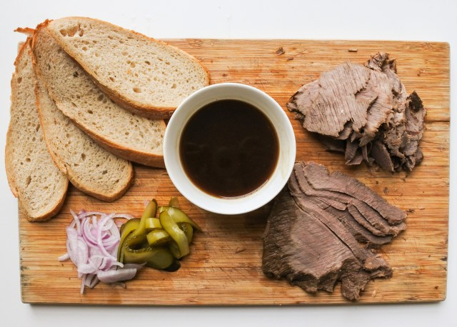Sliced rye bread, sliced red onions, sliced pickles and sliced brisket on a wooden cutting board with a bowl of dark gravy