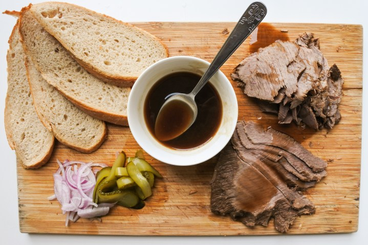 Sliced rye bread, sliced red onions, sliced pickles and sliced brisket on a wooden cutting board with a bowl of dark gravy and a spoon