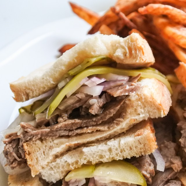 A sandwich with sliced brisket, gravy, sliced pickles and onions served alongside homecooked french fries