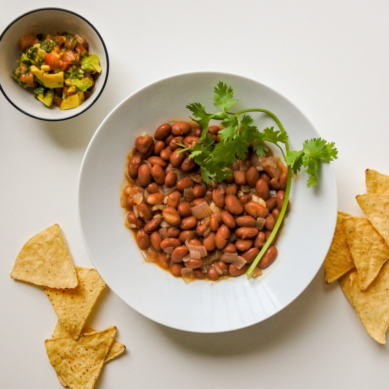 A bowl of brown taco beans garnished with a sprig of cilantro served alongside scattered tortilla chips and a pico de gallo