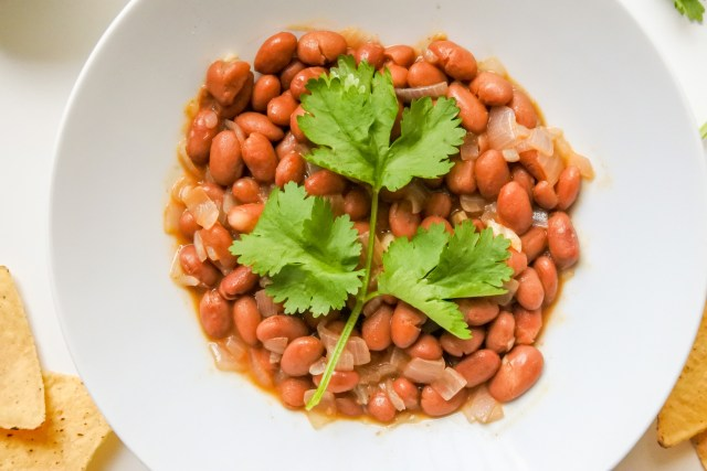 A bowl of brown taco beans garnished with a sprig of cilantro served alongside scattered tortilla chips