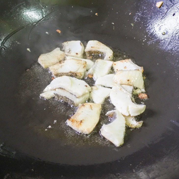 Slices of fish frying in oil in a large wok