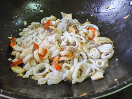 Squid, prawns and fish frying in oil in a large wok