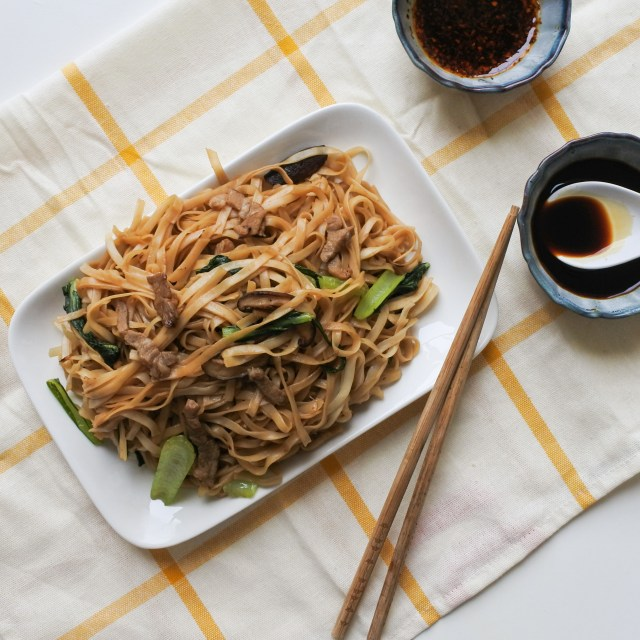 A plate of Shanghai Noodles with Chinese Chile Oil and black vinegar on the side
