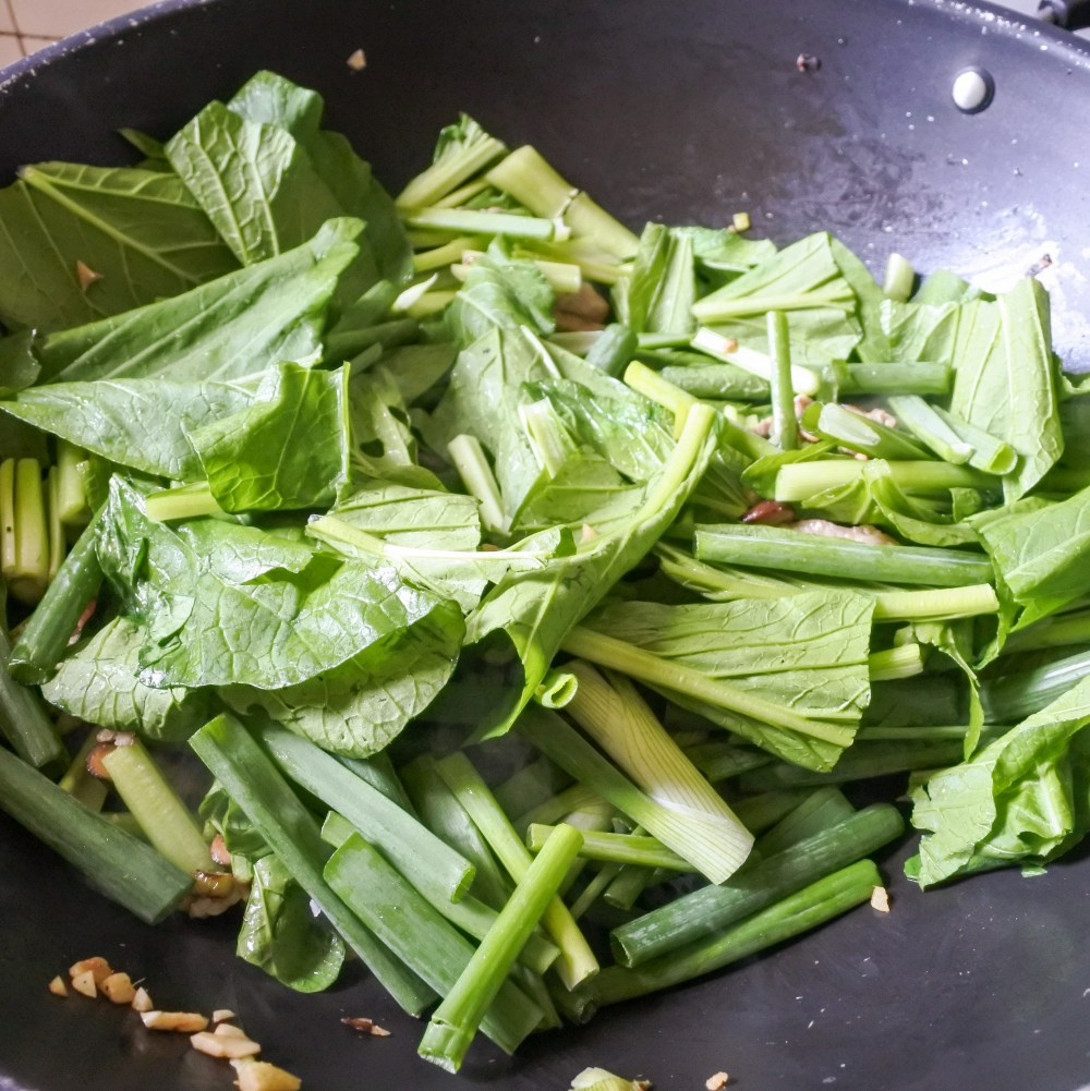 Chopped choy sum cooking in a wok with pork and mushroom mixture