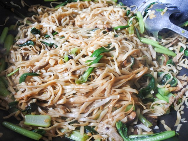 Soy sauce and sugar added to Shanghai noodles mixture in a wok.