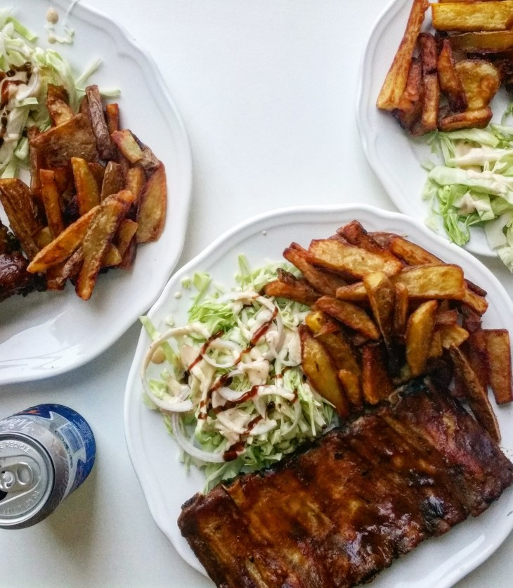 ribs on plates with french fries and coleslaw