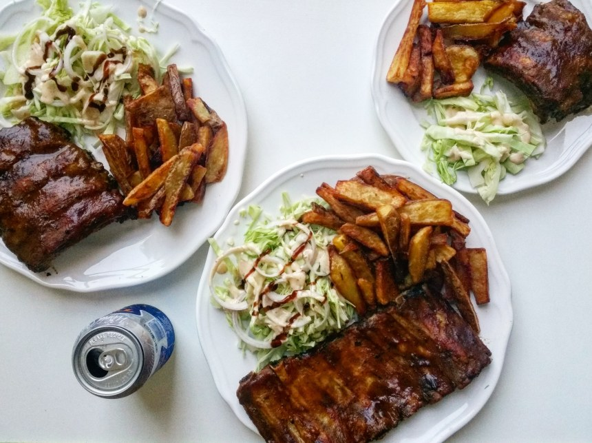 Pork ribs coated in BBQ sauce with french fries and coleslaw