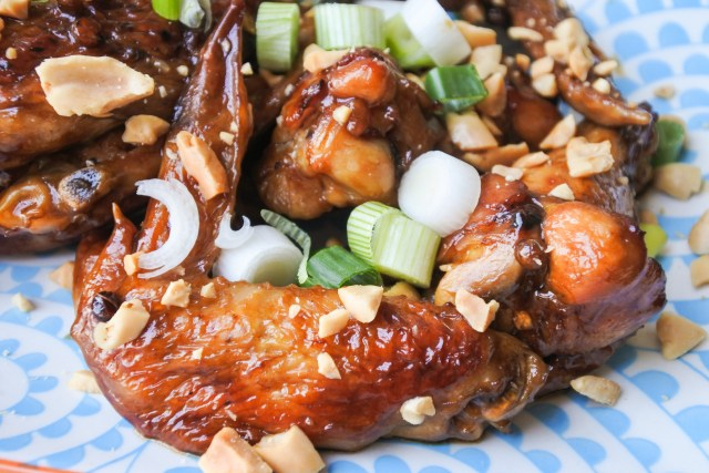 A pile of chicken wings garnished with peanuts and scallions