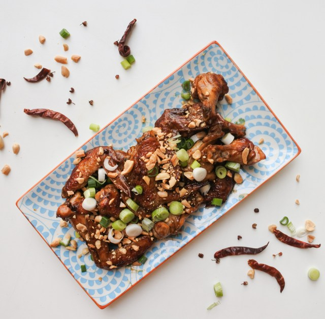 A plate of golden brown and spicy Kung Pao Chicken Wings topped with peanuts, scallions and chile peppers
