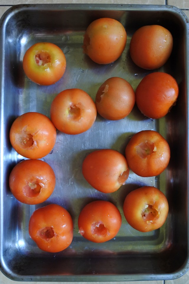 A tray of red tomatoes in a metal oven tray with stem removed