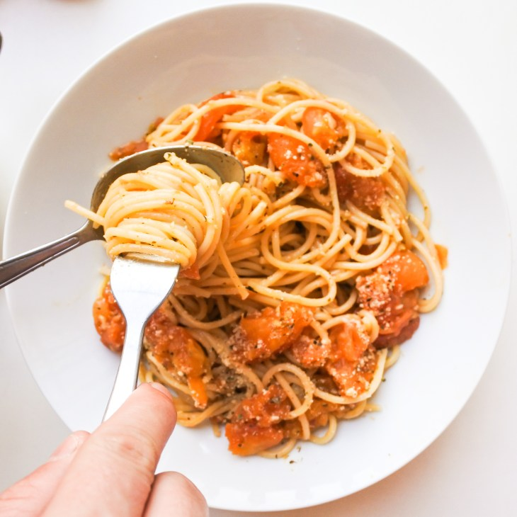 A fork twirling spaghetti tossed in a roasted tomato and anchovy sauce
