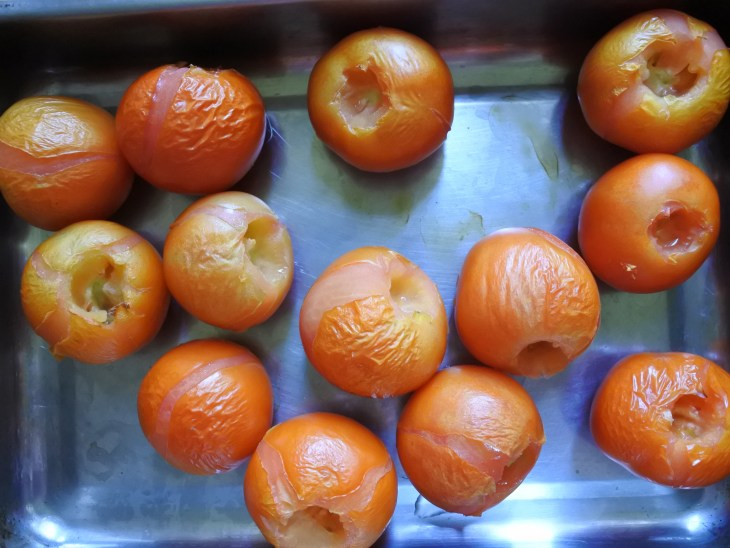 A tray of roasted red tomatoes with stem removed in an oven tray