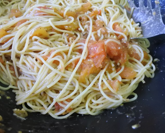 Cooked spaghetti tossed in the roasted tomato, garlic and anchovies sauce in the pan