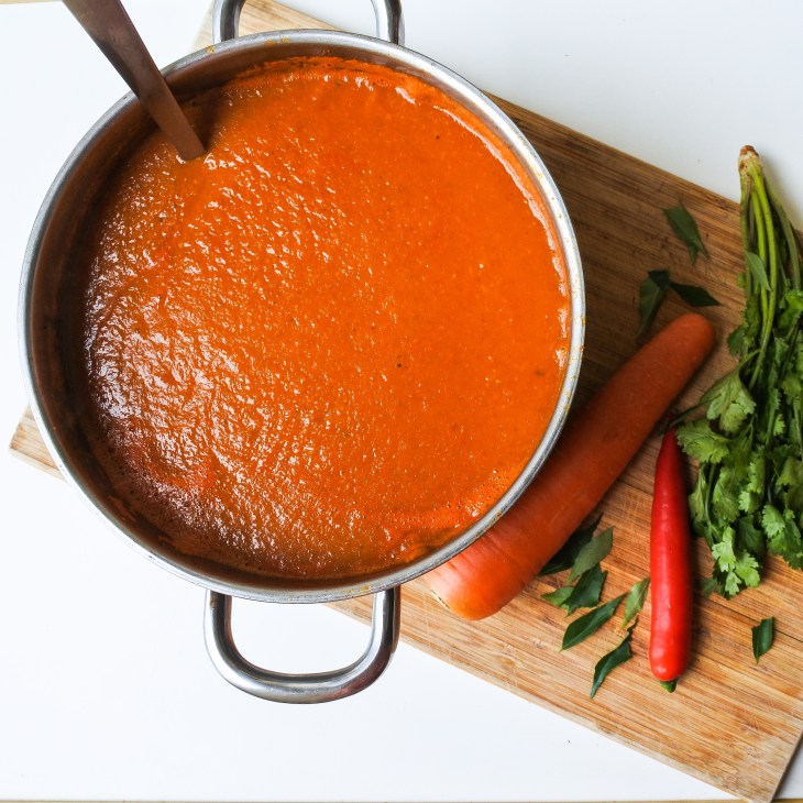 ladle in base gravy for a curry with vegetables