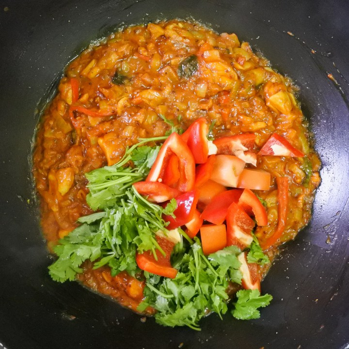 roughly chopped tomato, red bell pepper and cilantro added to chicken balti
