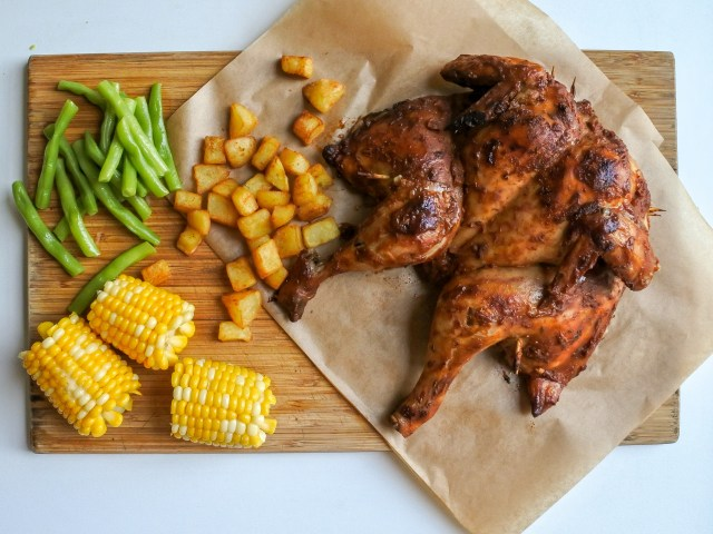 spatchcock chicken on cutting board with fried potatoes, corn and green beans
