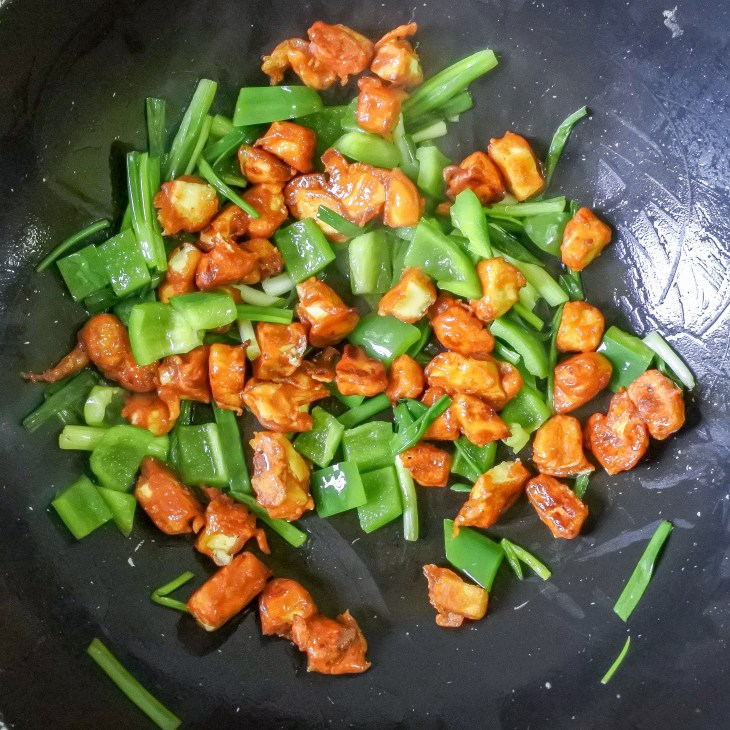 Fried paneer stir frying in a wok with bell pepper and scallions