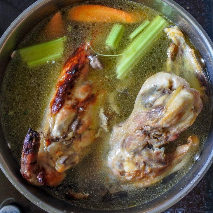 chicken carcasses, vegetables and water in stockpot