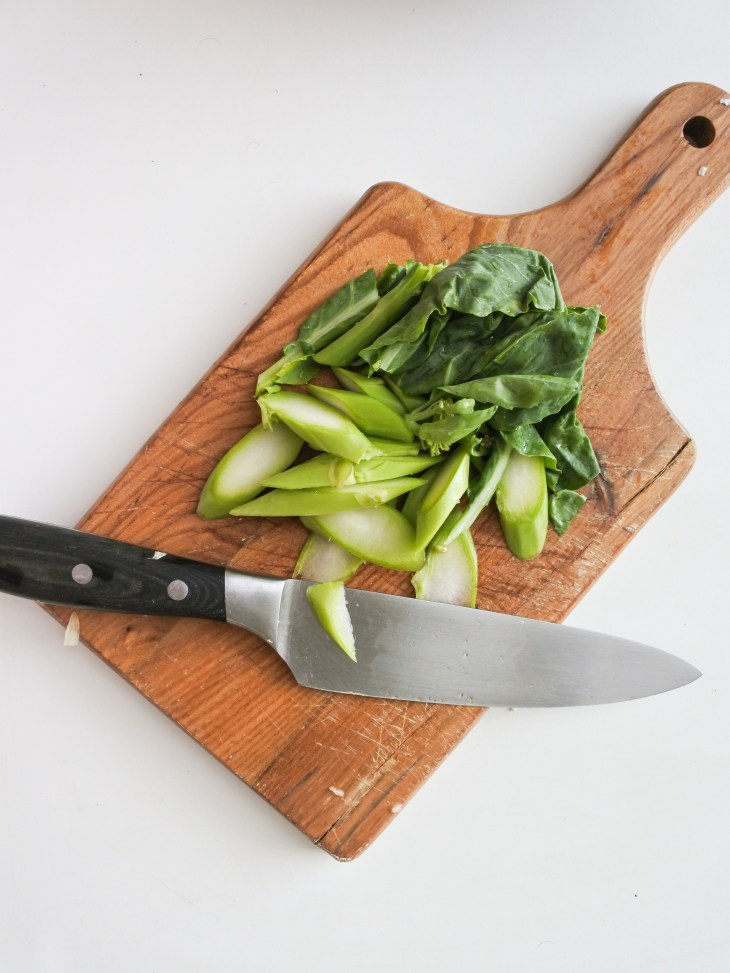 chopped kailan on a cutting board with knife
