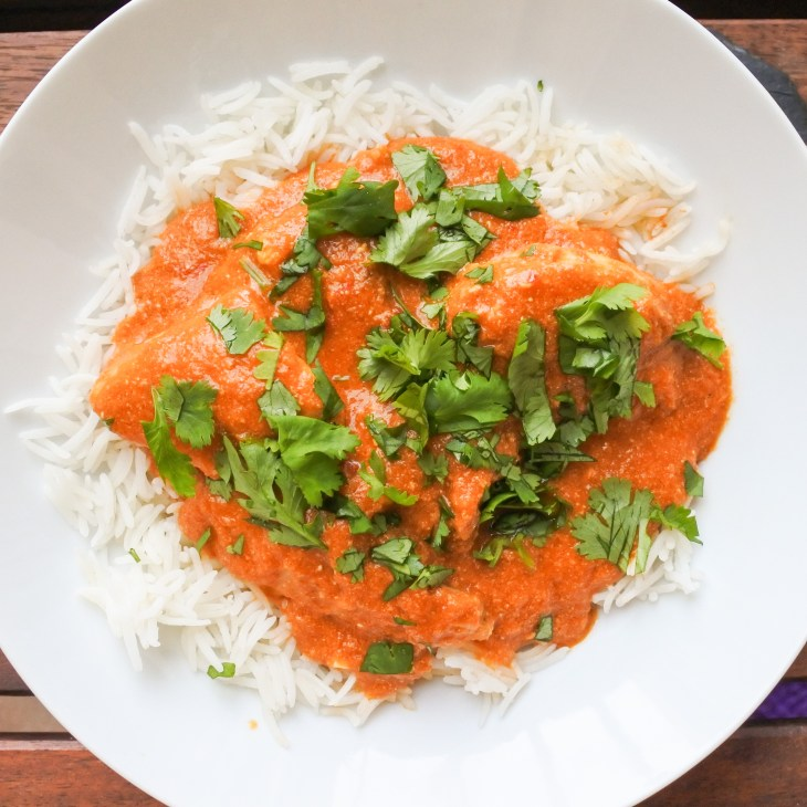 curry over Basmati rice in a bowl garnished with chopped cilantro