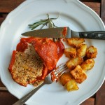 lamb stuffed red bell pepper on a plate with roast potatoes