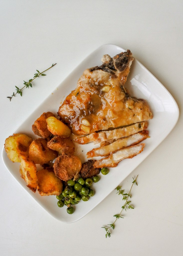 sliced fried pork chop with sauce on a plate with roast potatoes and peas