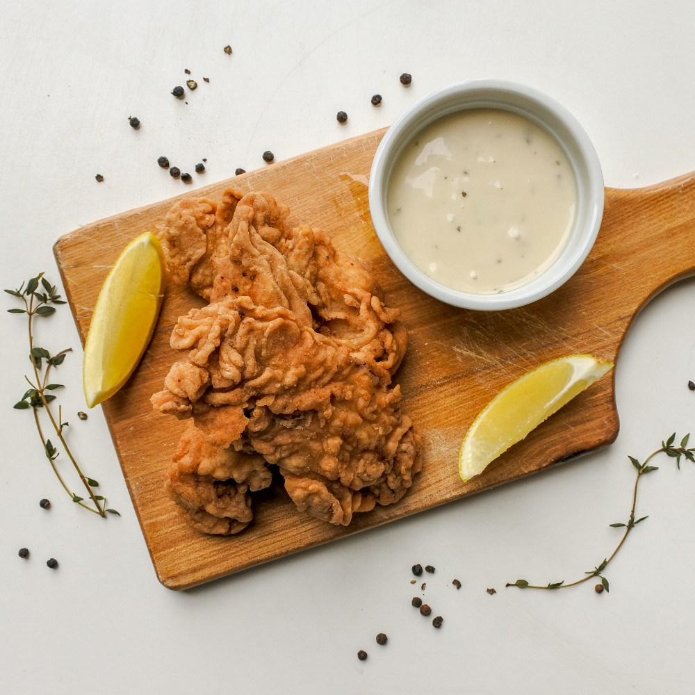 Crispy chicken tenders on a wooden board with lemon wedges and ranch sauce with thyme sprigs and black peppercorns