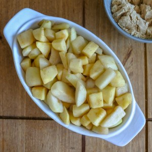 apples and pears tossed with spiced butter in a baking dish on a wooden table