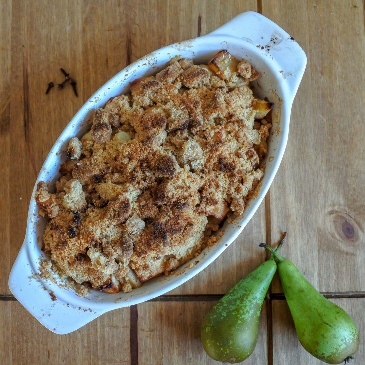 Baked apple and pear crumble with cloves and pears on a wooden table