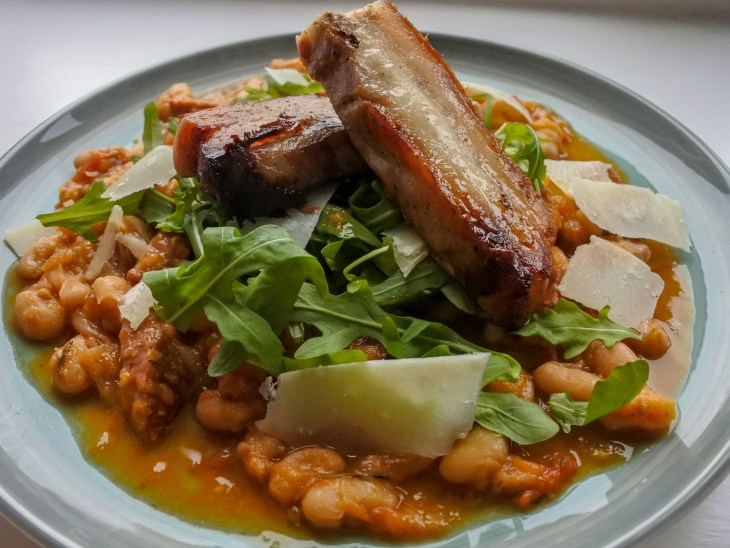 Chorizo cassoulet topped with wild rocket, Parmesan shavings and sliced pork belly