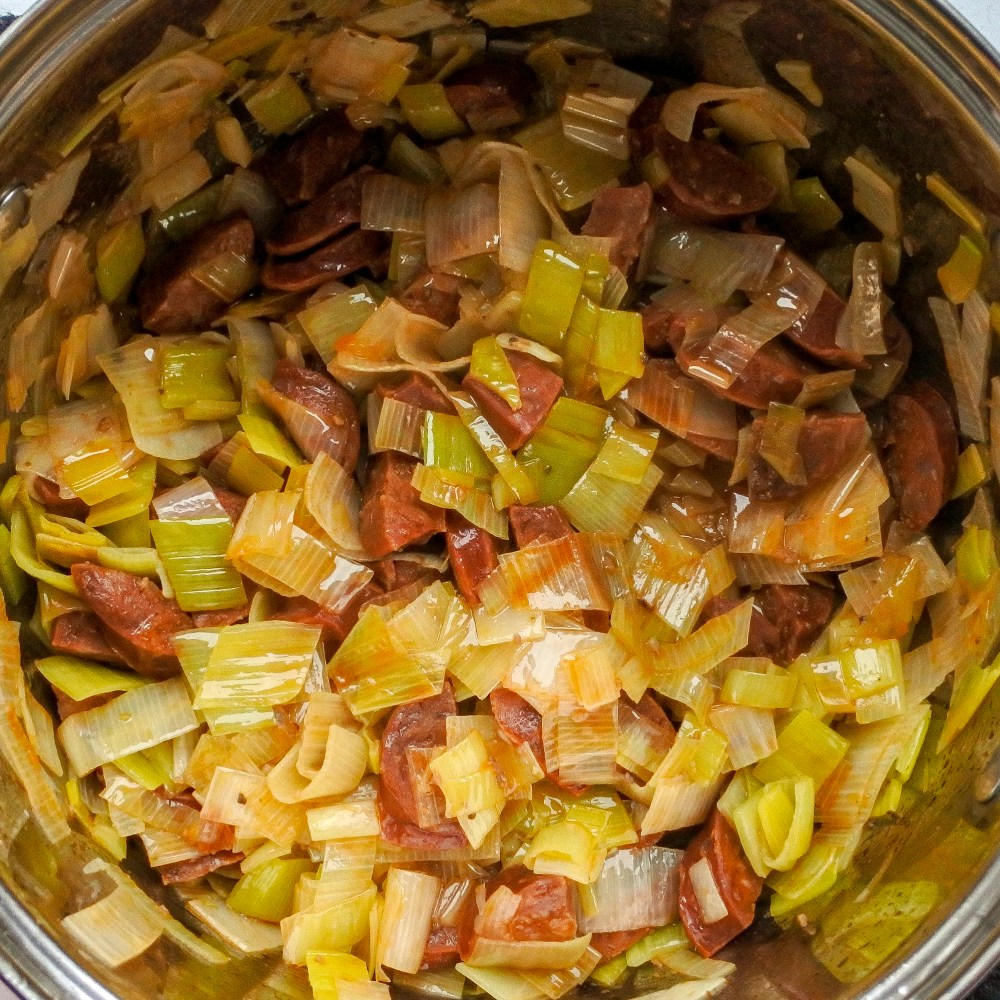 Chopped leek, minced anchovies and diced chorizo cooking in a pot
