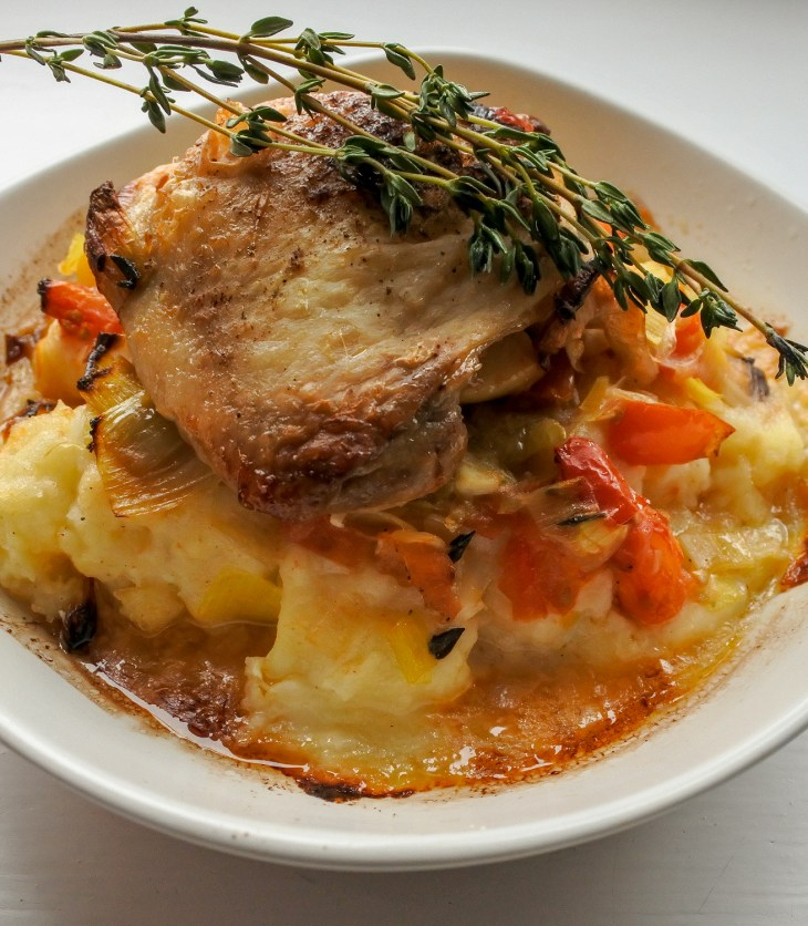 Crispy chicken thighs stuffed with apple and bacon over mashed potatoes with leeks and tomatoes garnished with a sprig of thyme