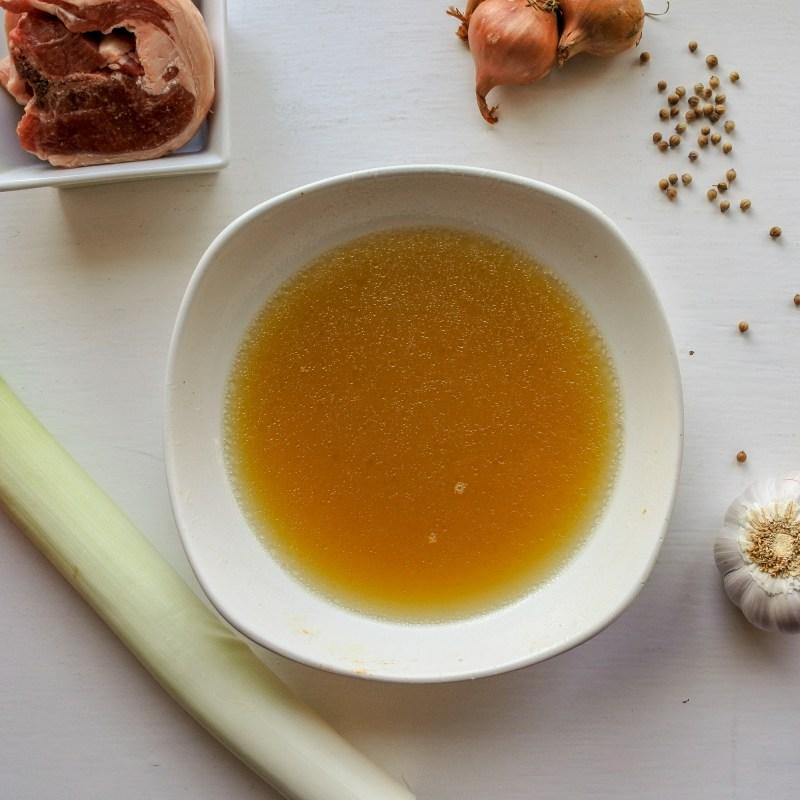 lamb stock in a bowl next to lamb, leek, shallots, garlic and coriander seeds
