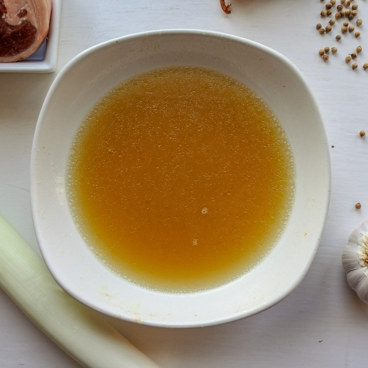 stock in a bowl next to lamb, leek, garlic and coriander seeds