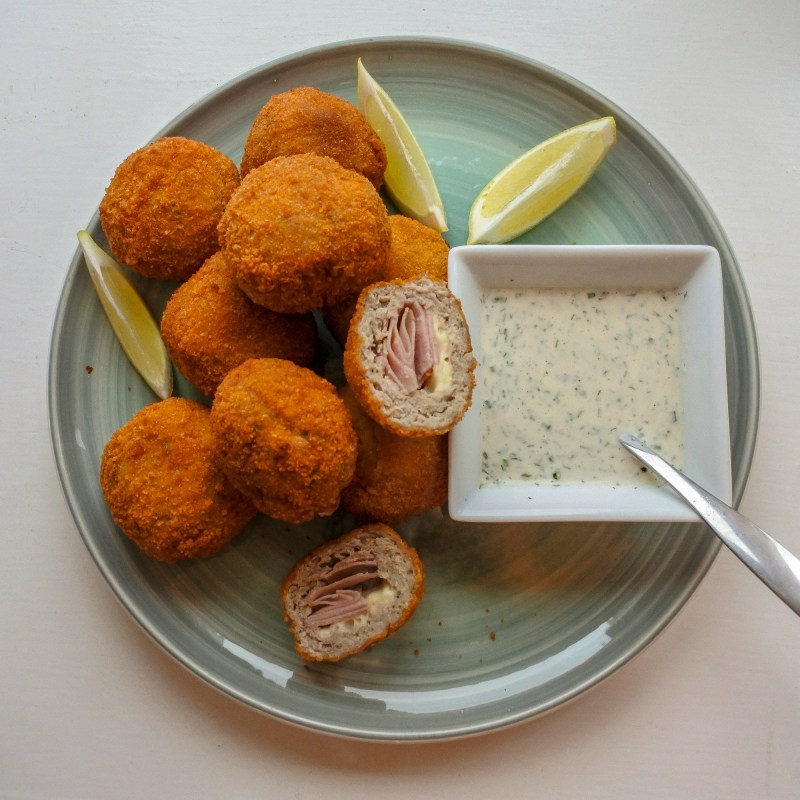 Chicken cordon bleu bites on a plate with slices of lemon and ranch dipping sauce