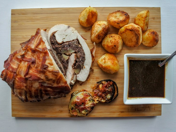 bacon wrapped stuffed turkey breast with roast potatoes, gravy and roasted onions