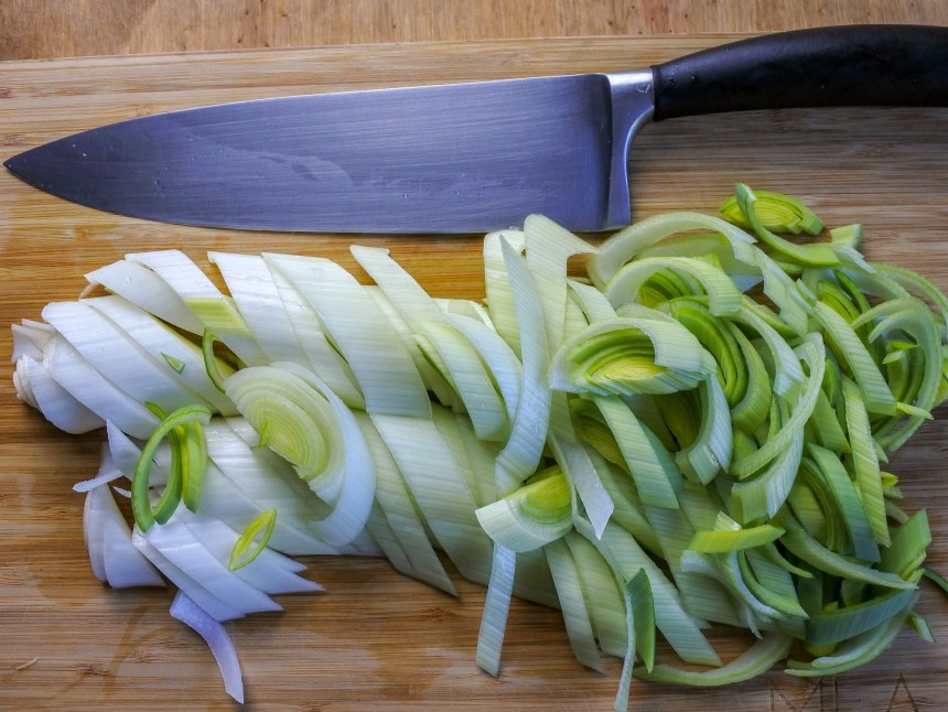 a leek finely sliced on a wooden cutting board