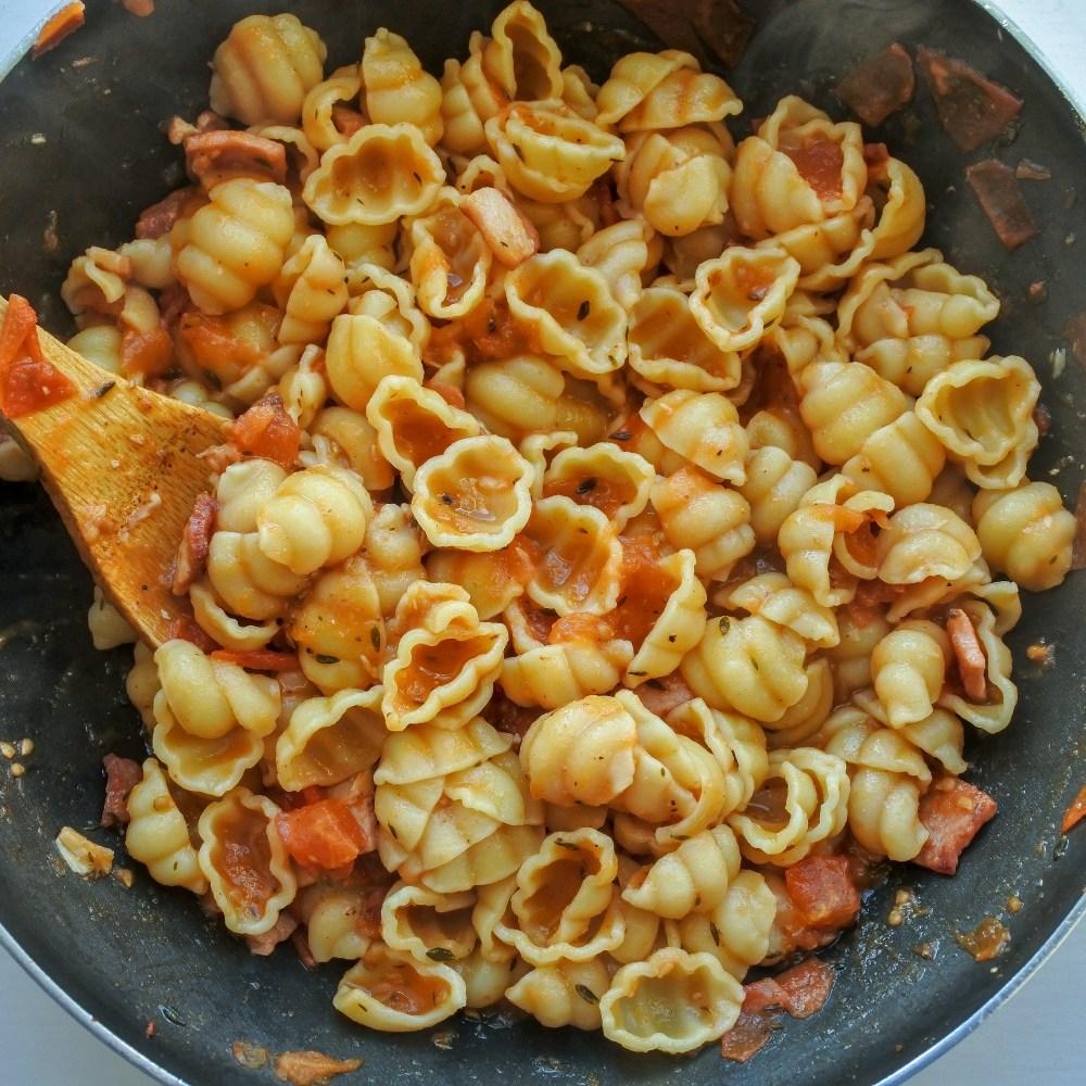 shells tossed with sauce in a pan with a wooden spoon